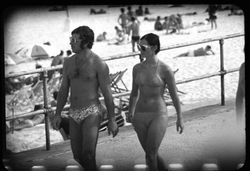[Man and woman walking down Bondi Promenade]
